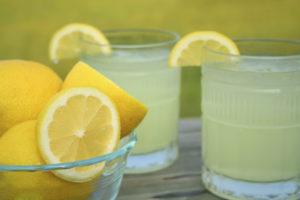 Two glasses of fresh lemonade and a bowl full of lemons outside on a summers day.